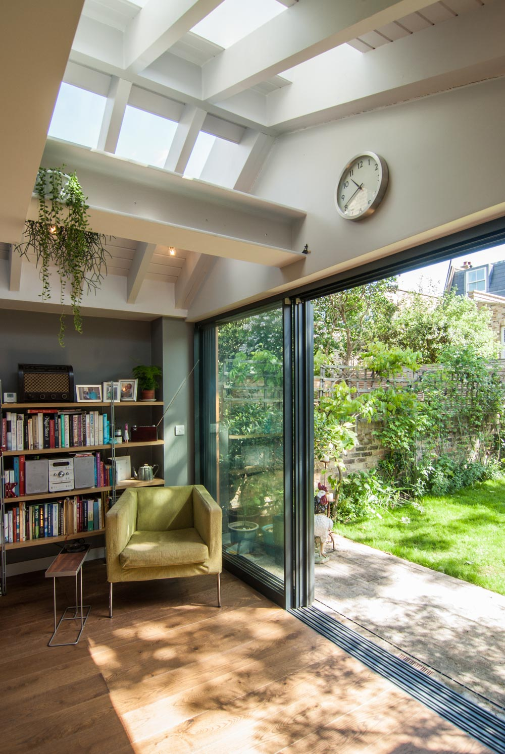 Roof lights above the exposed steel joists add drama. Seamless threshold between kitchen and garden.