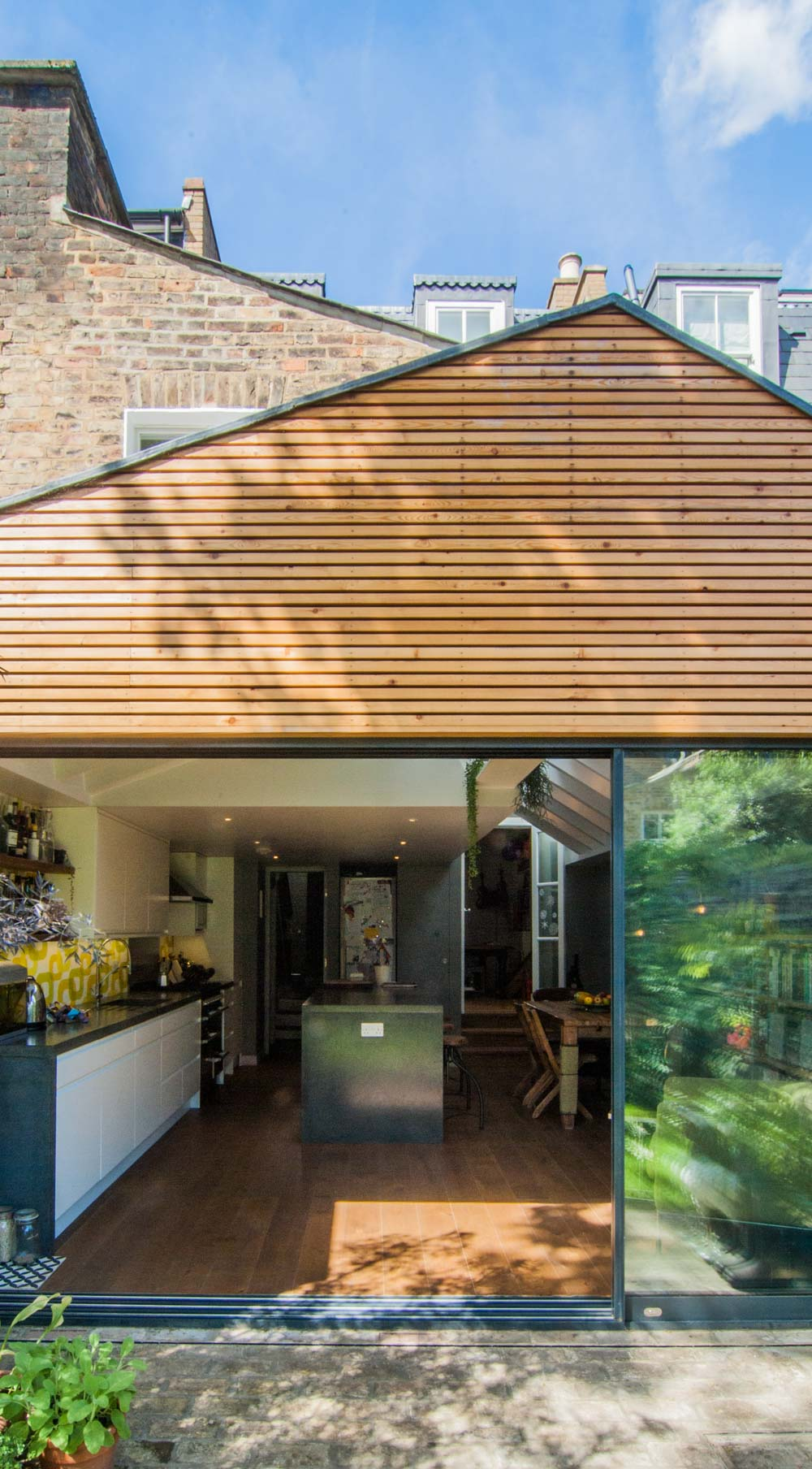 Garden & kitchen are seamlessly connected in this gabled rear extension in Hackney.