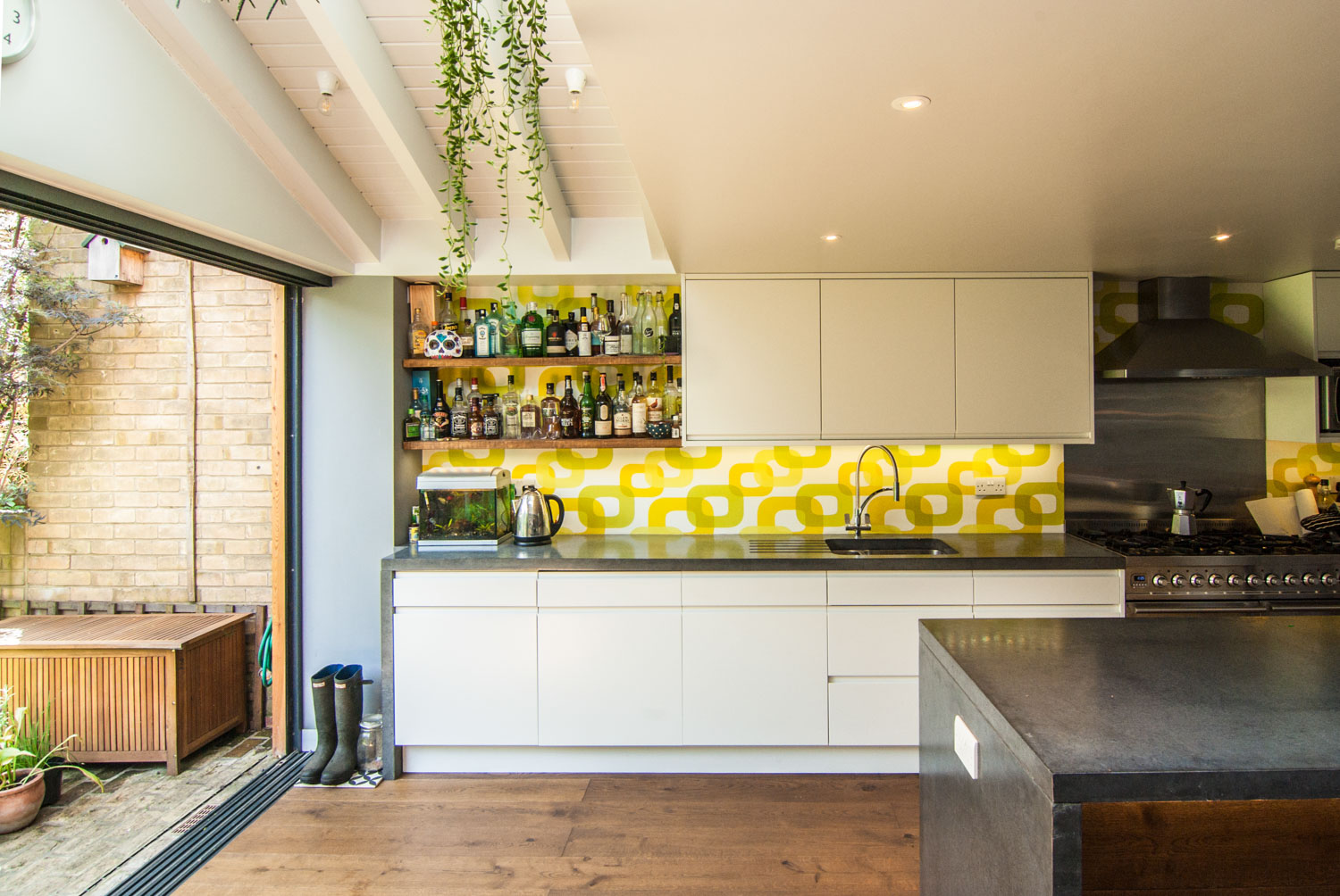 Bespoke kitchen and black polished concrete island by the dining area.