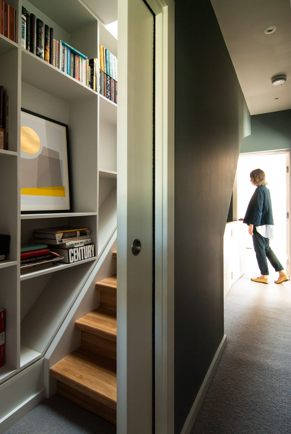 hidden timber staircase sliding door shelving