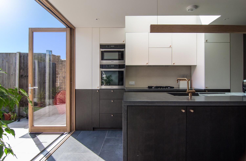 Mortise concrete worktop black MDF concreto strata tile vola brass tap buster+punch handles bi-fold door