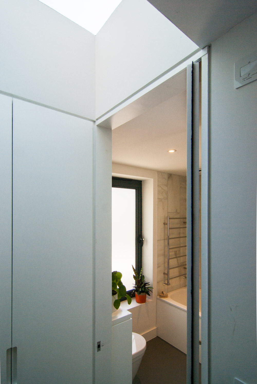 Full height pivot door by large storage in the hallway.