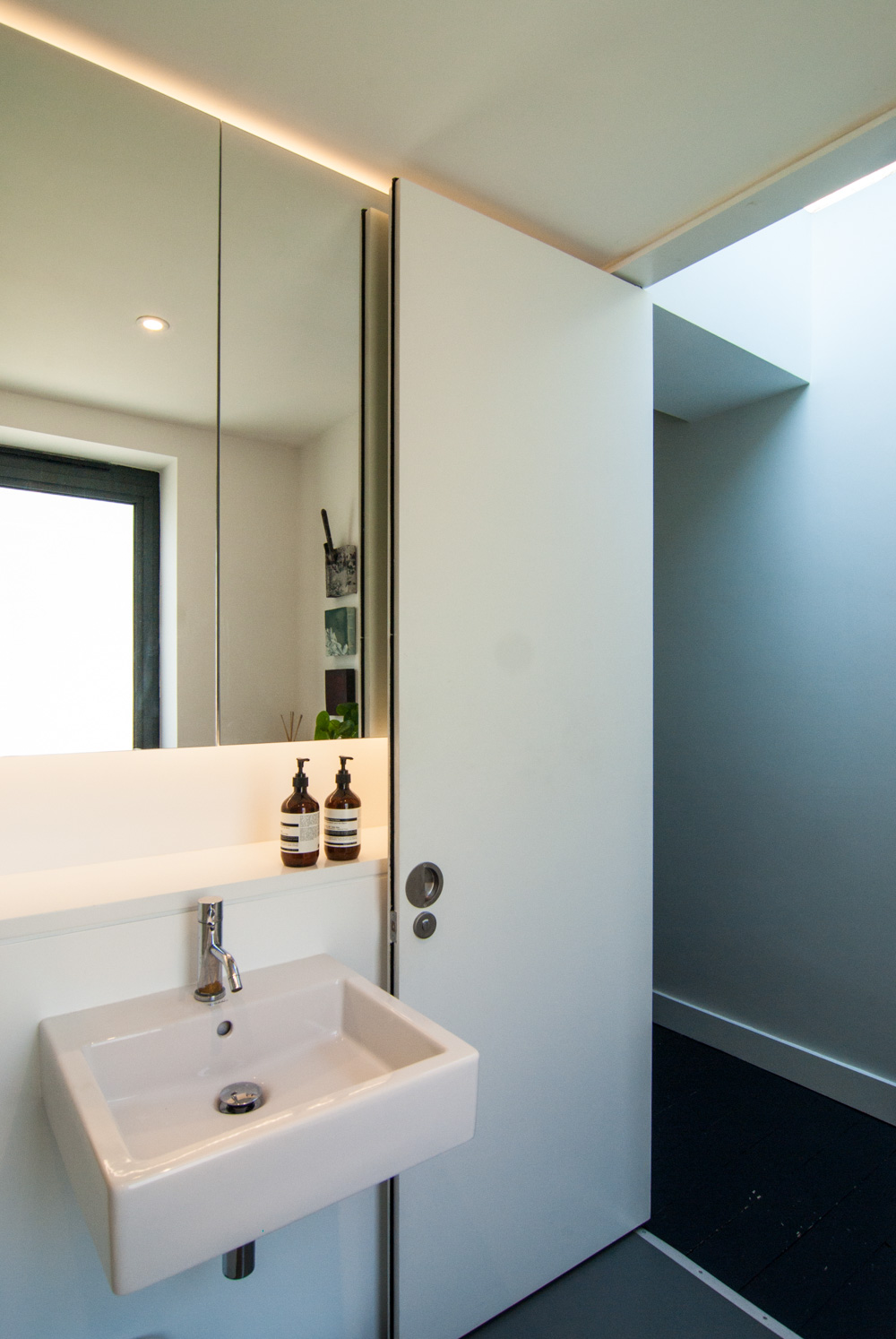 Mirror cabinet with bespoke shelf lit with LED by a full height pivot door and roof light in the hallway.