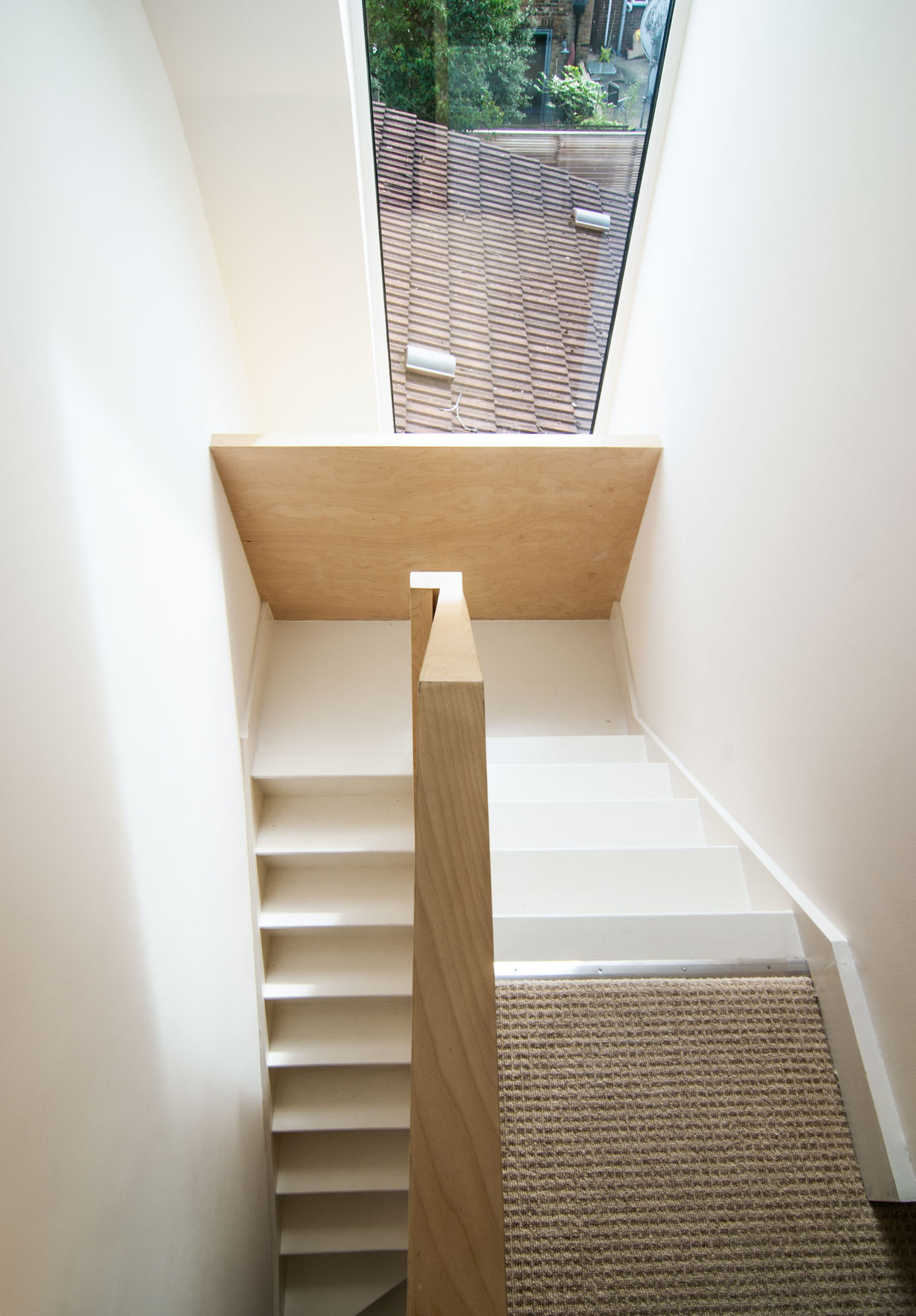 Large window allowing plenty of sunlight to shine inside the house and onto the bespoke plywood balustrade.