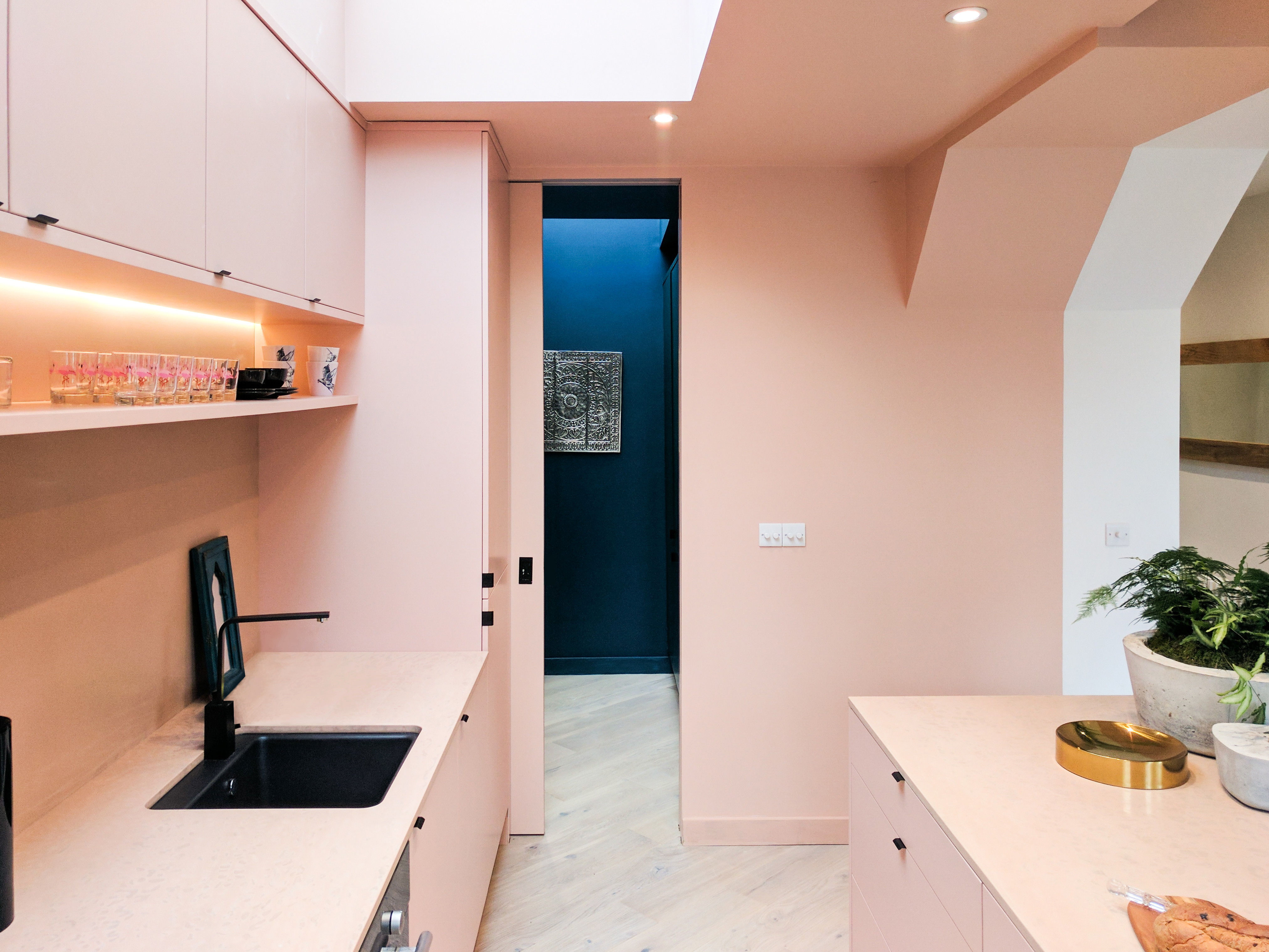 Blush pink kitchen compose beautifully with the black sink and fittings.