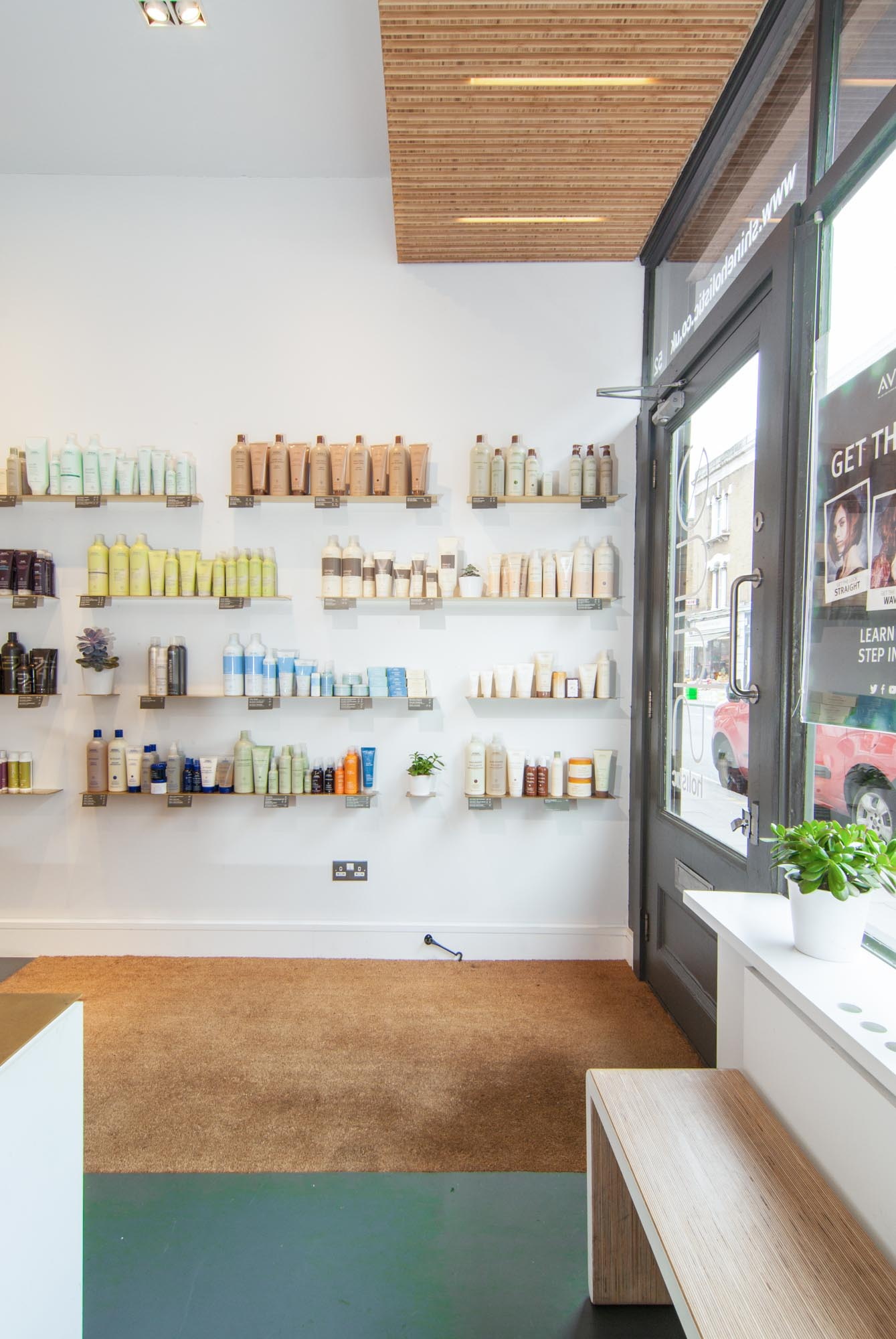 Brass shelving by the entrance of Shine Holistic Hairdresser salon.