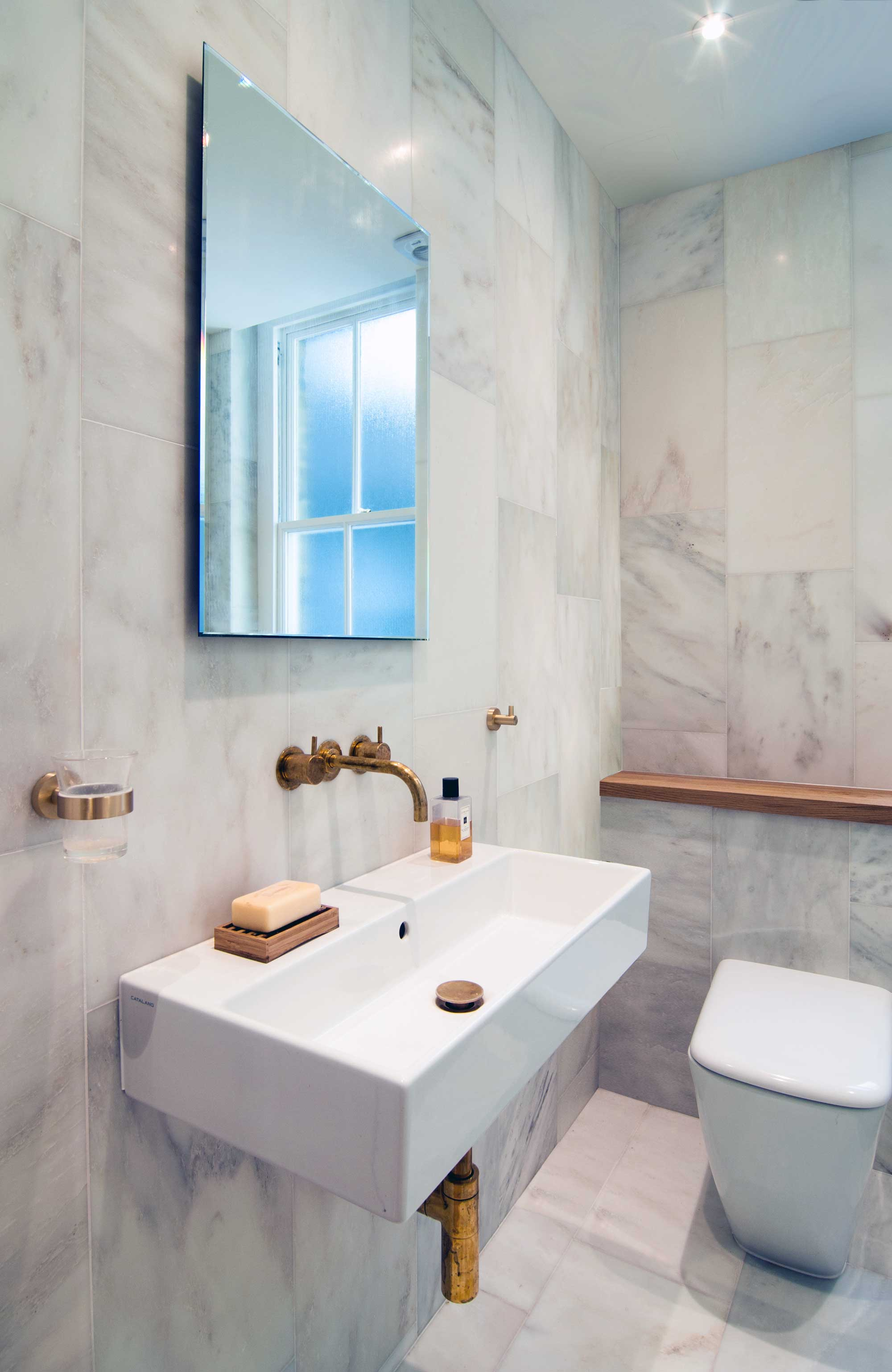 Carrara marble tiles on the walls and floor and Vola brass taps are what make this bathroom so unique and original.