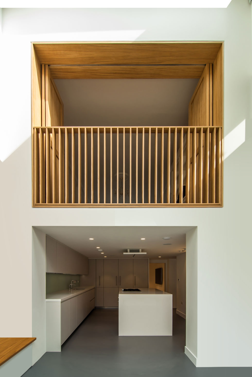 Internal balcony consisting of an Oak shutter frame balustrade being the focus amongst the white walls.