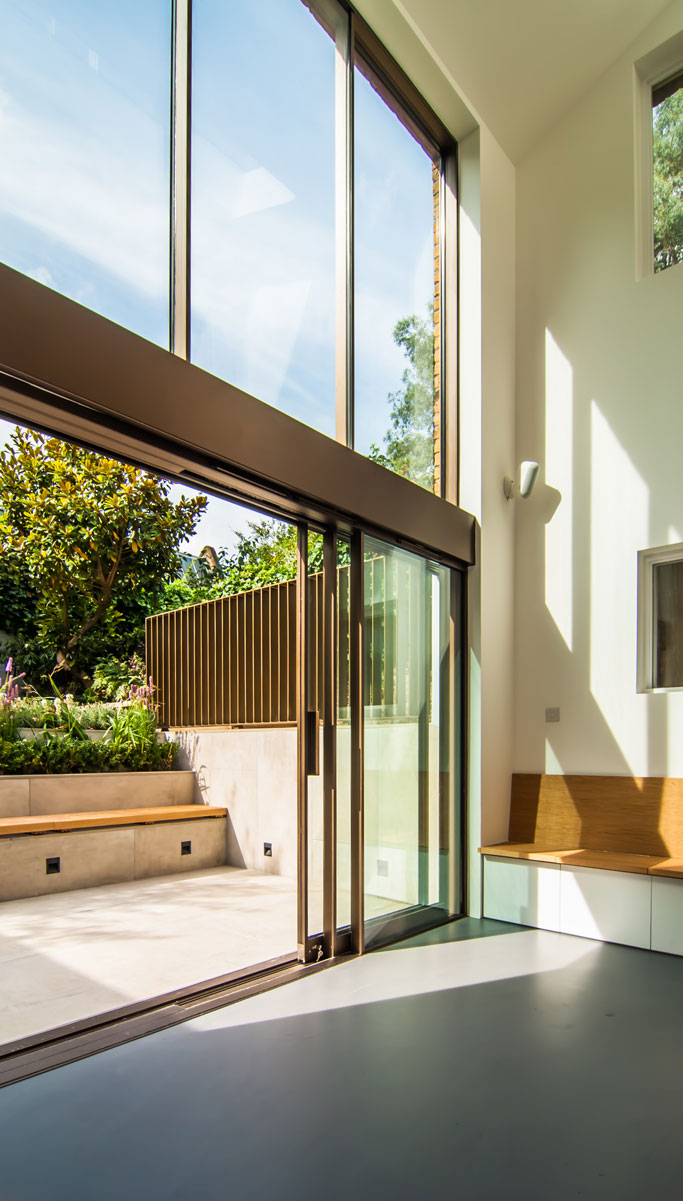 Double height space including a sunken courtyard and built in bench in the interior of the extension.