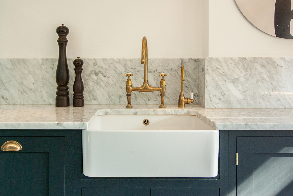 Beautiful gold sink battery and marble worktop work perfectly with the teal kitchen cabinets.