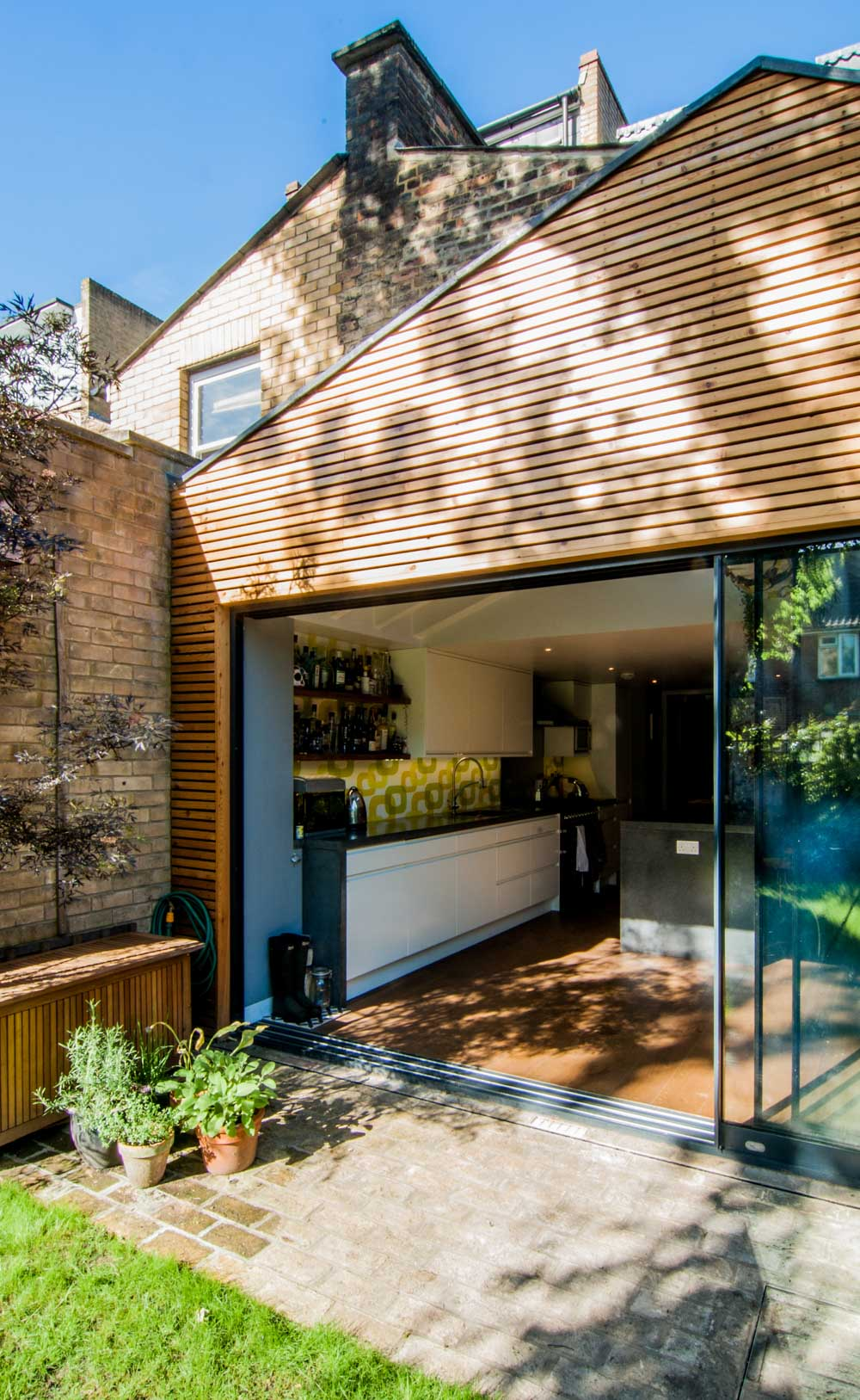 Timber cladding rear extension including large sliding doors overlooking the garden.