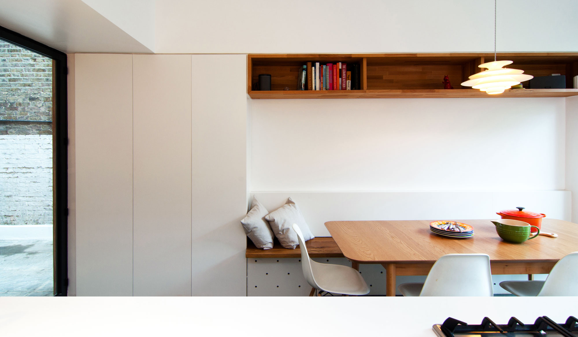 New kitchen extension highlighting key details such as the timber bookshelf and bench within the white contemporary storage cabinets.