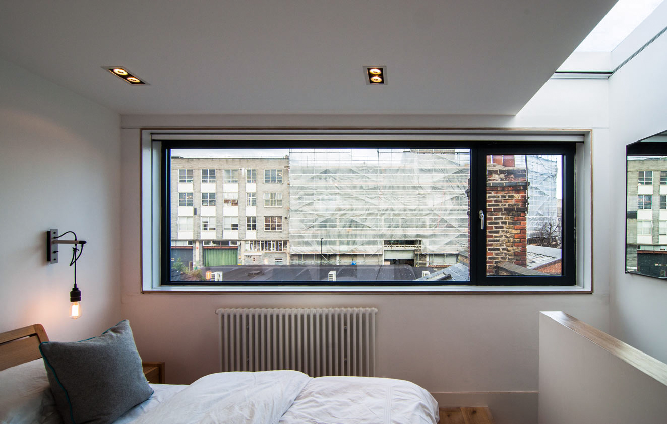 Large horizontal bedroom window and roof light with minimal artificial lighting in the converted loft bedroom.