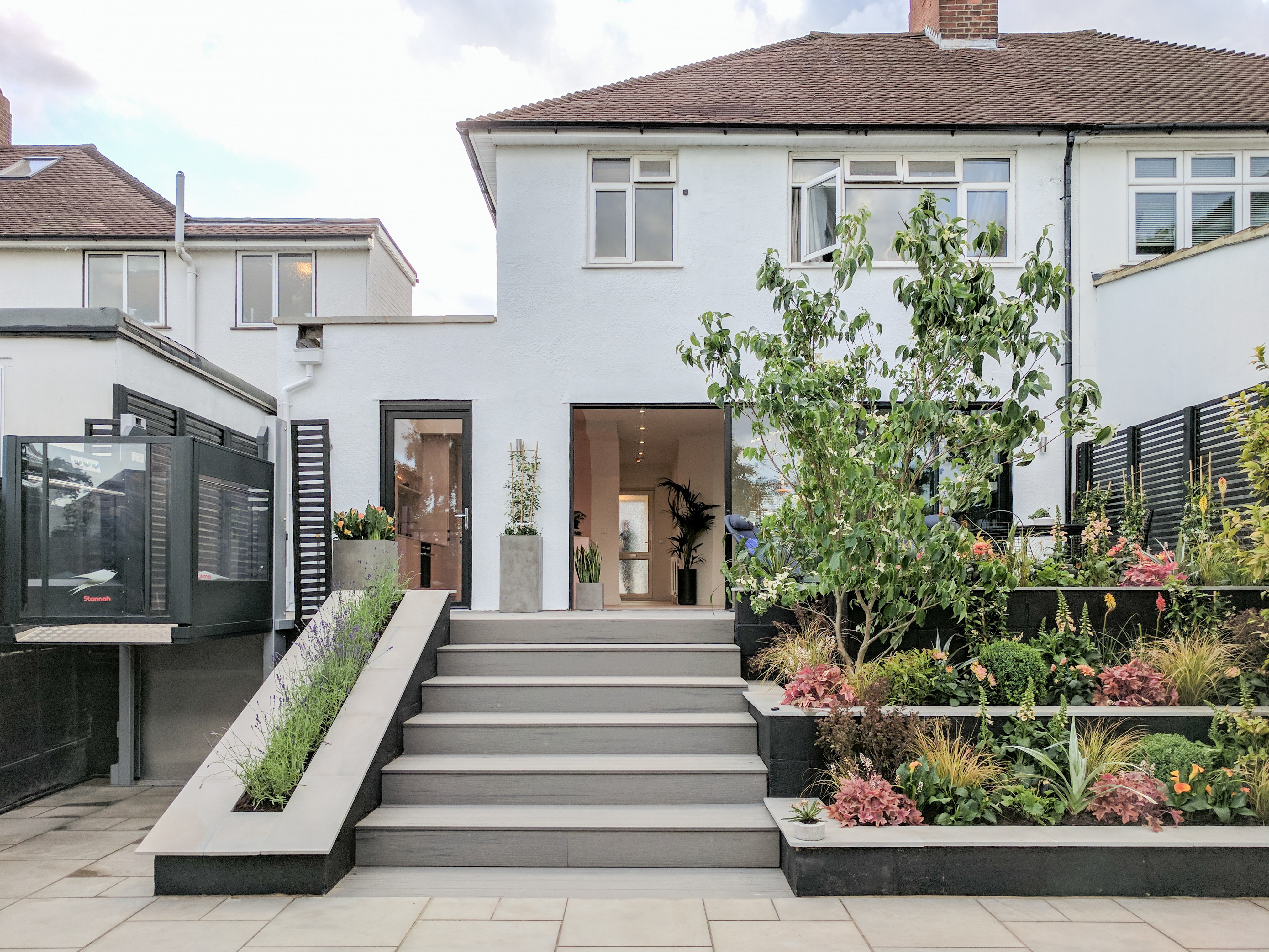 Front facade of the refurbished house including large sliding doors and planting.