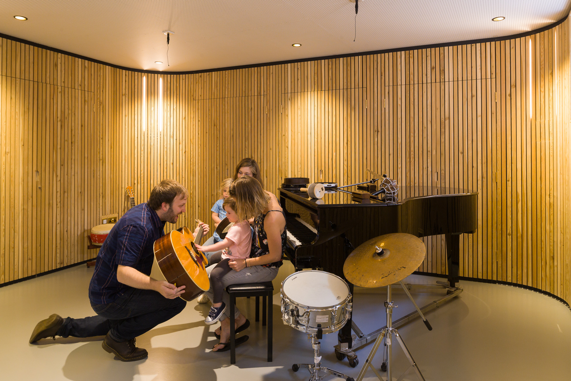 Children playing instruments in the music therapy room refurbished with walls layered with timber battens.