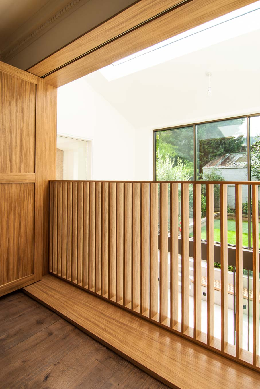 Close up of the Oak shutters balustrade and view onto the extension and sunken courtyard.