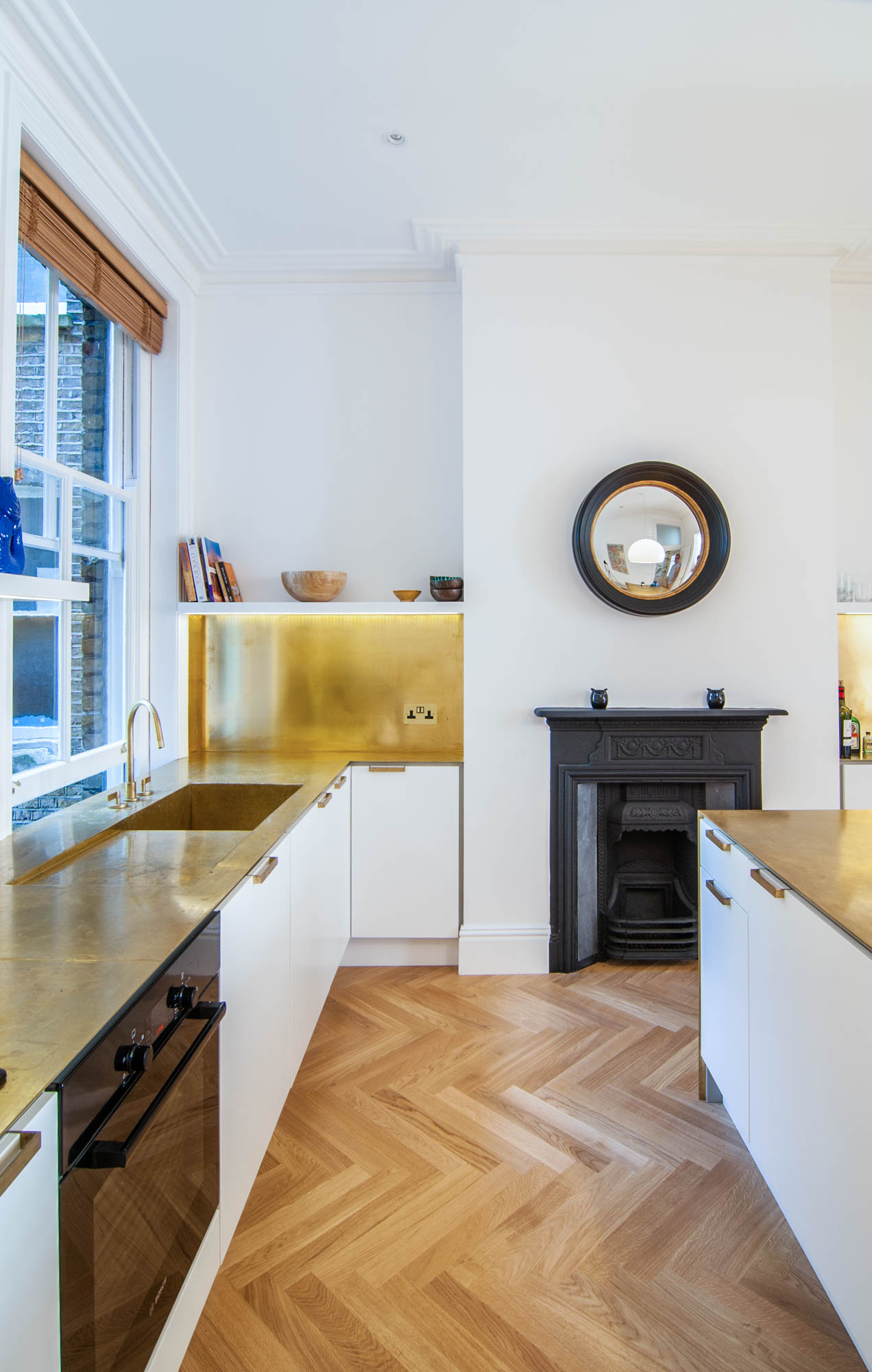 Beautiful brass gold worktops work perfectly with the parquet floors, white cabinets and black fireplace.