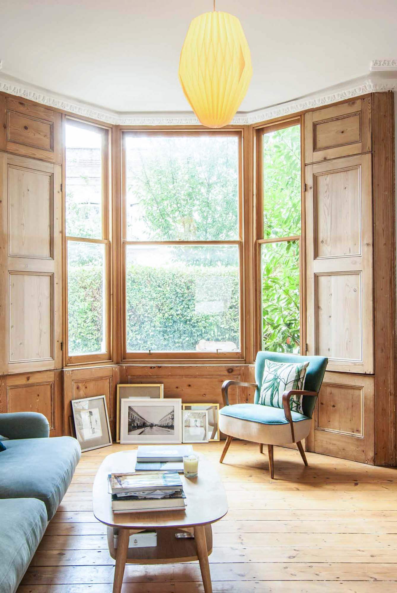 Photographer's House: Beautiful timber room with large windows allowing plenty of light to come through. Green sofa and armchair fitting with the timber as well as the greenery outside.