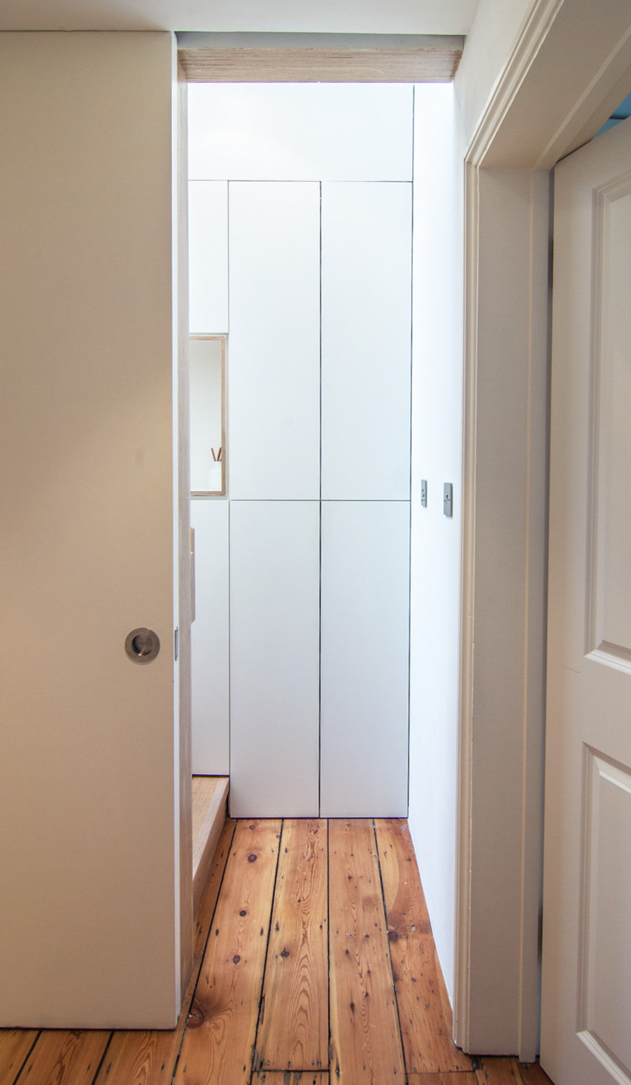 Rustic pine flooring contrasting with the white contemporary concealed door.