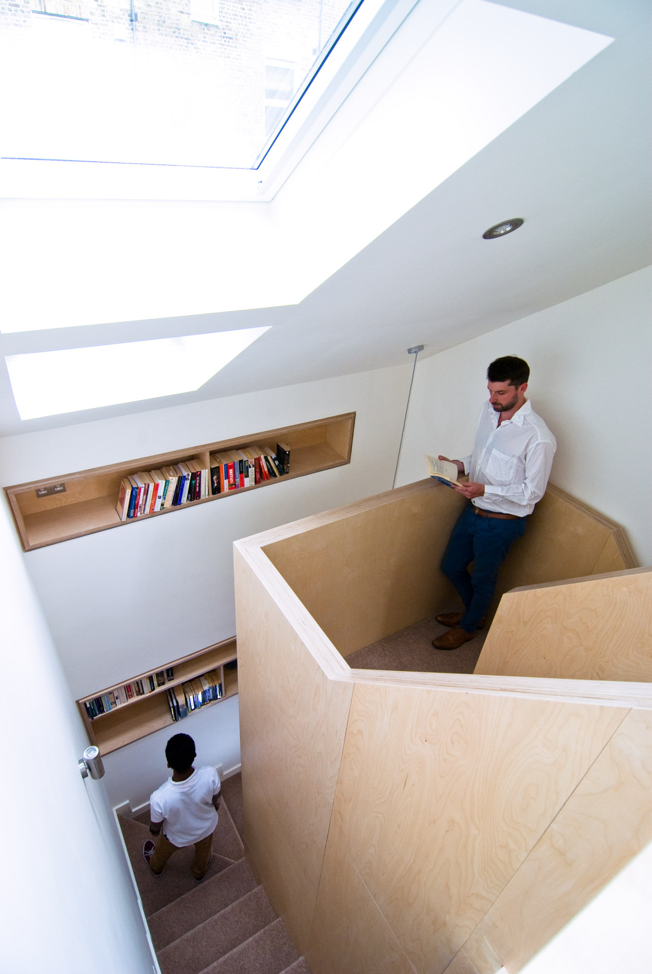 Original plywood staircase with plywood bookshelves incorporated into the walls.