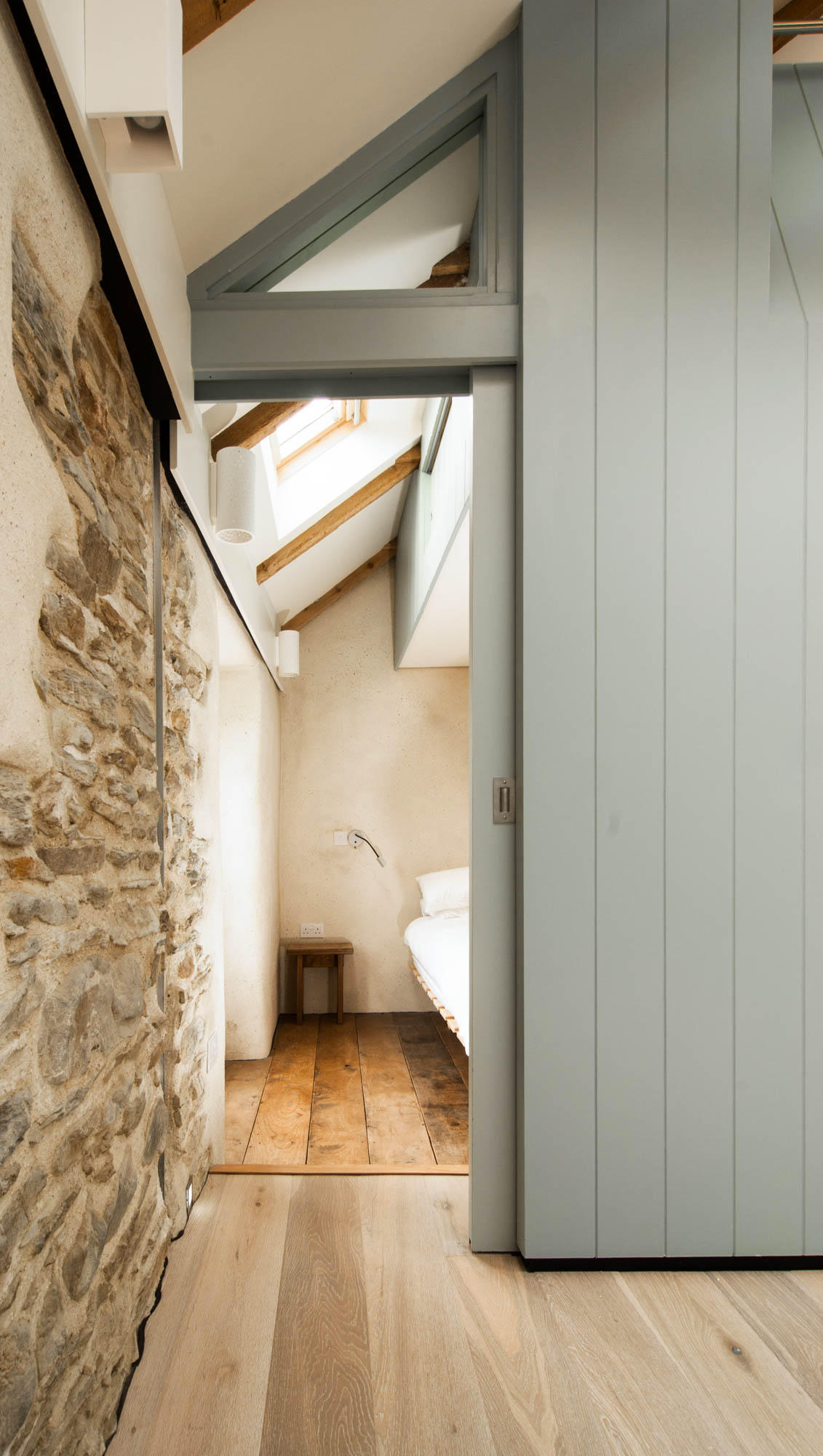 Contrasting light green beams and original stone walls.