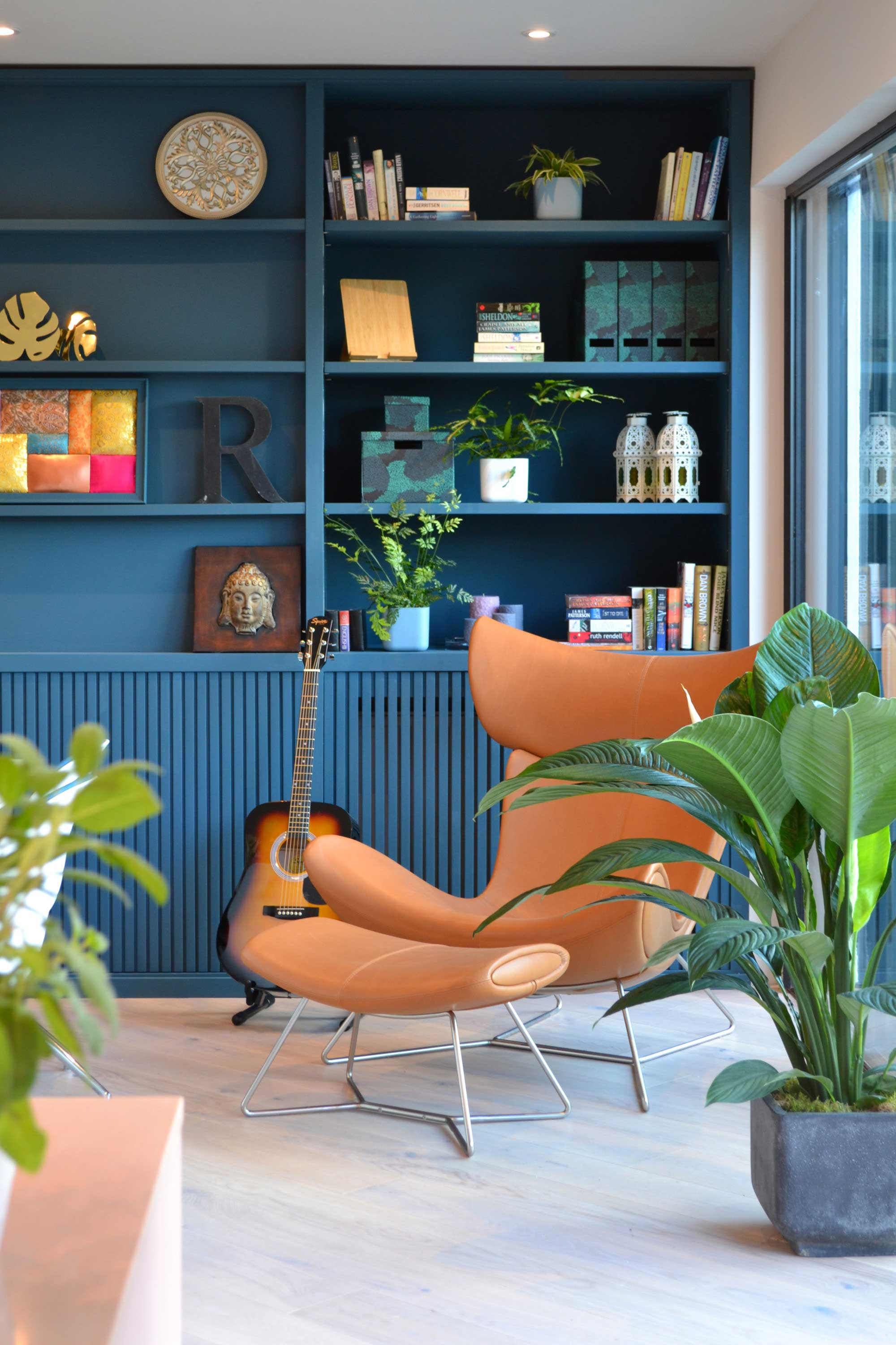 Love Your Home and Garden- Beautiful teal bookshelf and a coloured leather arm chair forming the perfect reading corner.