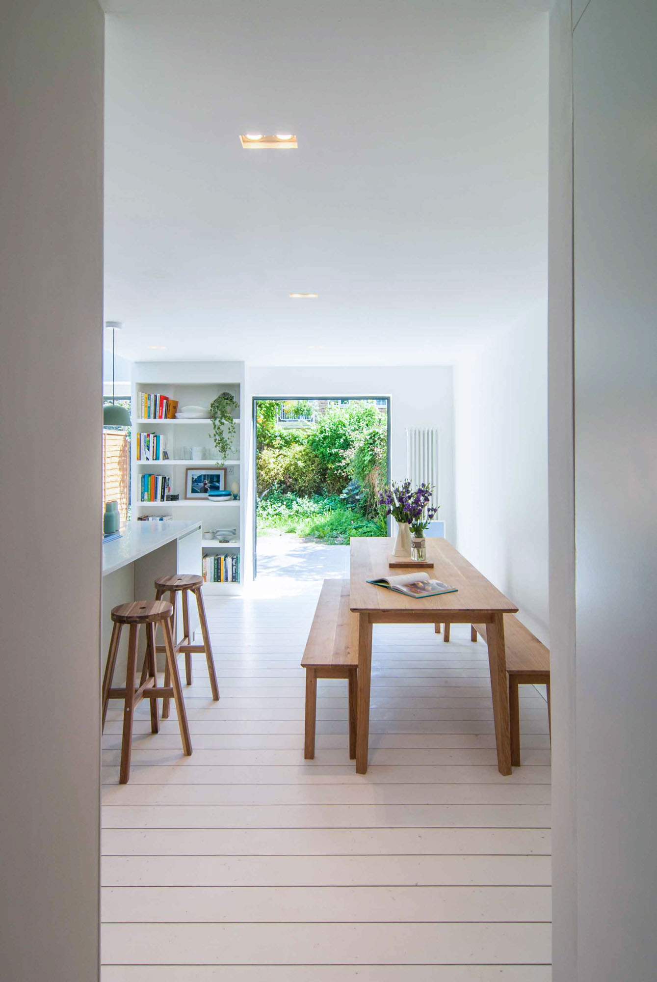 Photographer's House: View of the dining space opposite the kitchen overlooking a bespoke white bookshelf and large doors opening up to the beautiful garden.