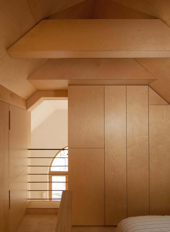 Plywood upper floor bedroom overlooking the downstairs living area and open plan kitchen.