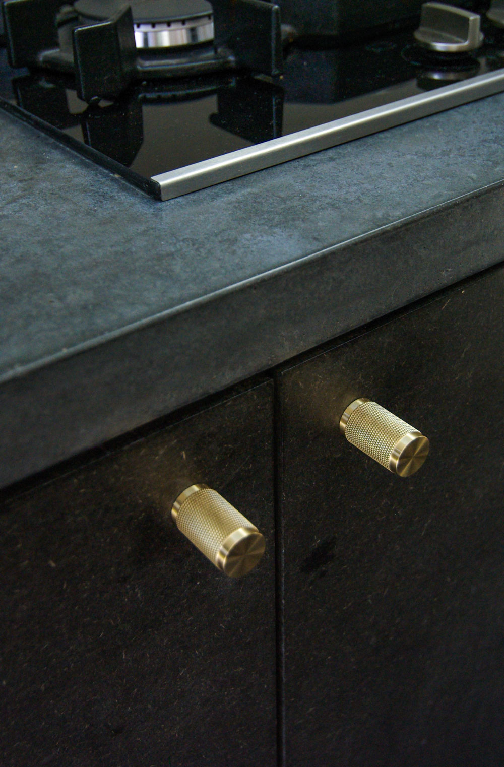 Close up of the concrete kitchen worktop and brass handles.
