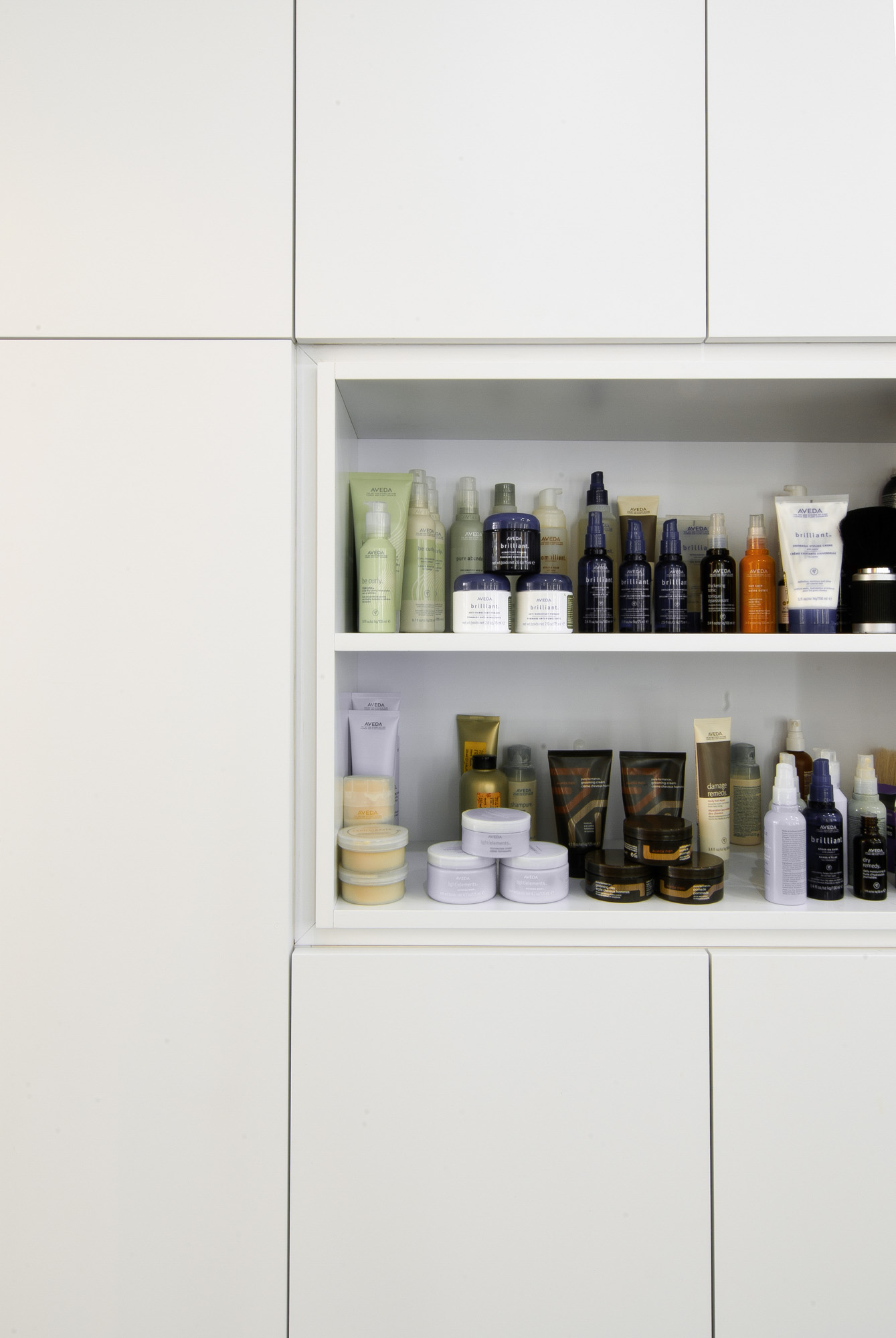 A close up of the bespoke joinery and contemporary storage units which hold hair care products.