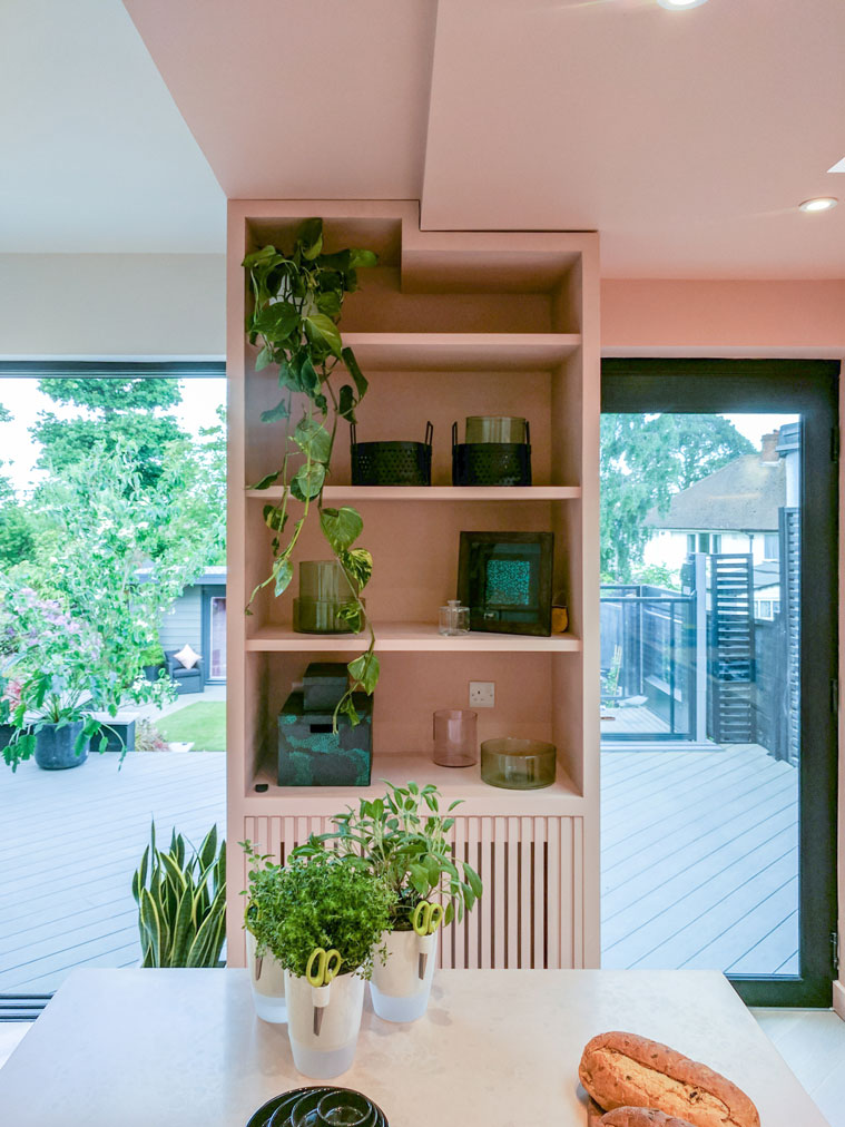 Love Your Home and Garden- Blush pink bookshelf splitting the kitchen.