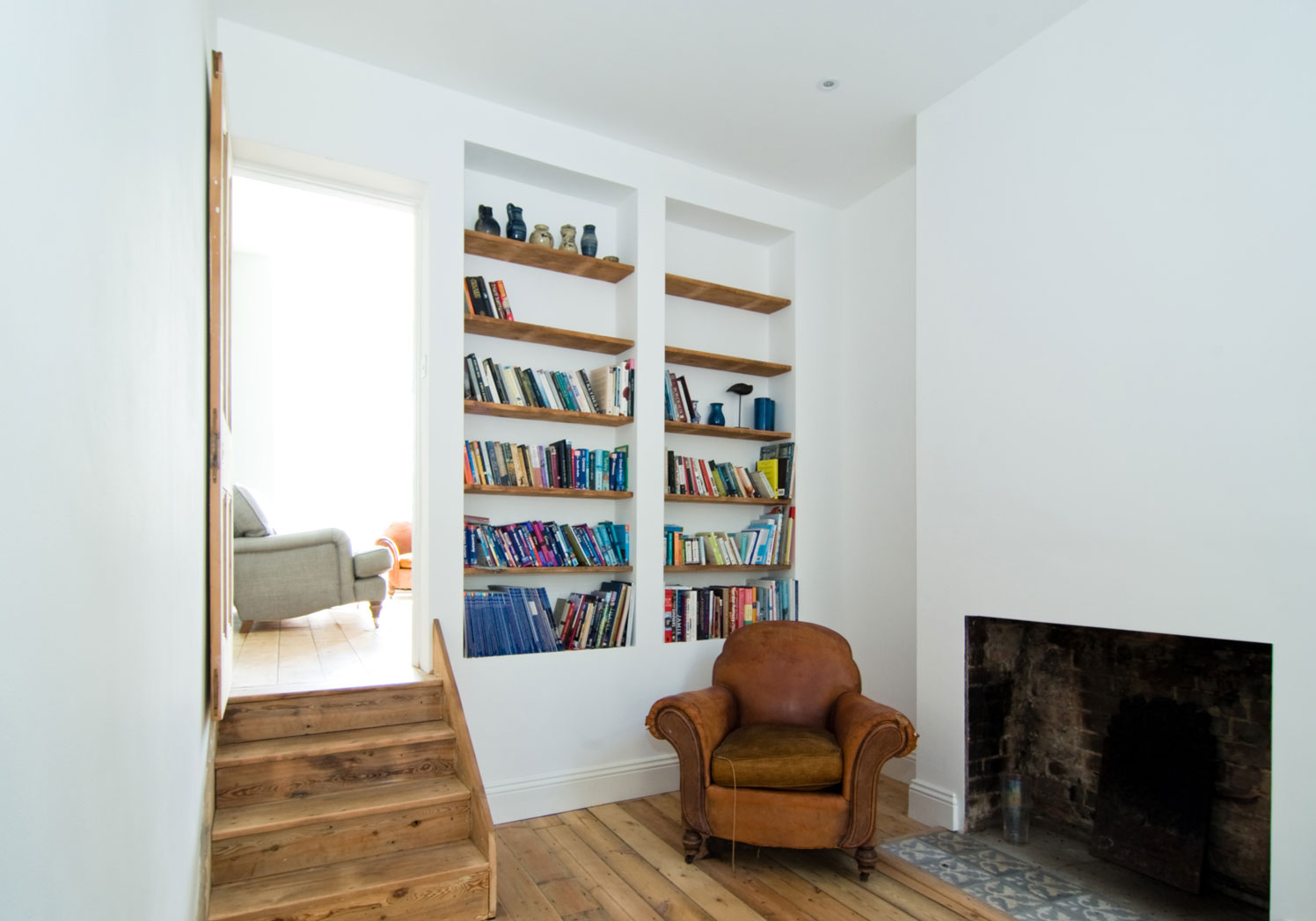 Rustic flooring and fireplace with a minimal bookshelf form a simple yet charismatic interior.