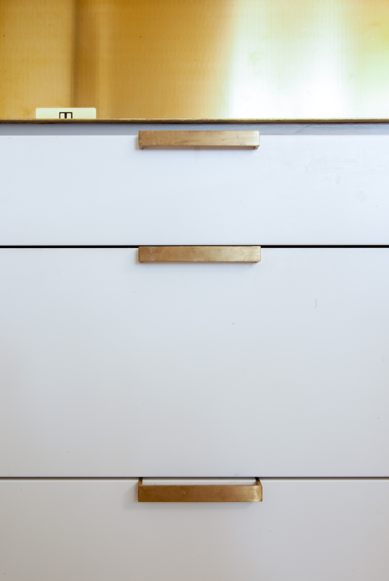 Close up of the bespoke handles along the brass worktop and white kitchen cabinets.