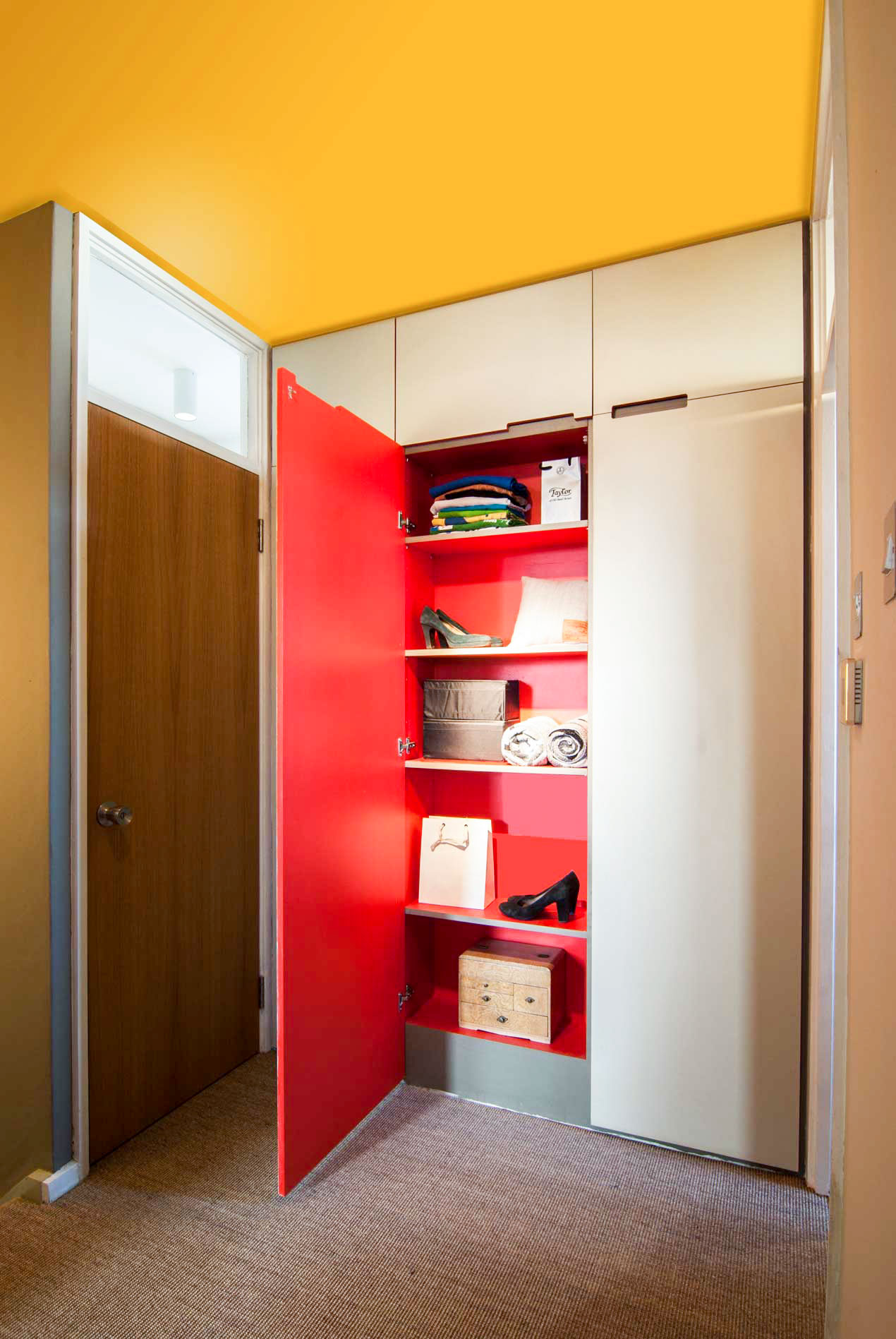 Bright coloured unique joinery cupboard offers plenty of storage space.