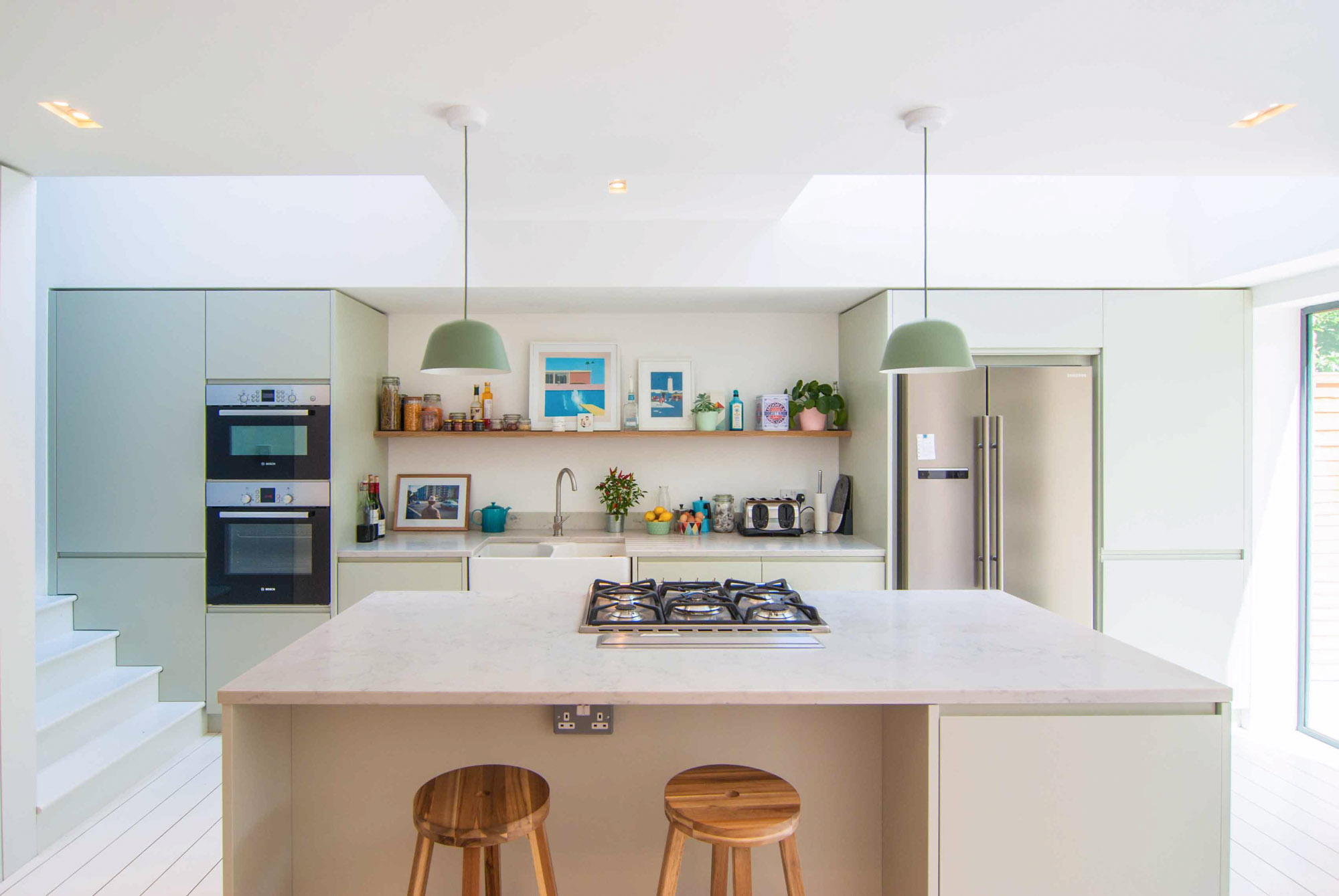 Photographer's House: Interior view of the side extension including a new kitchen with a pastel minimal colour palette.