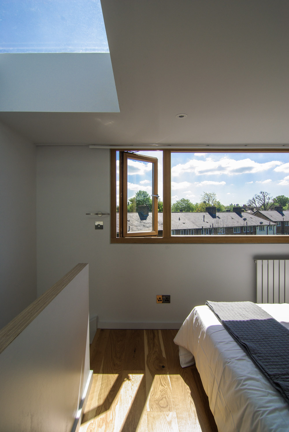 Loft extension bedroom filled with light coming through the roof light and oak windows.