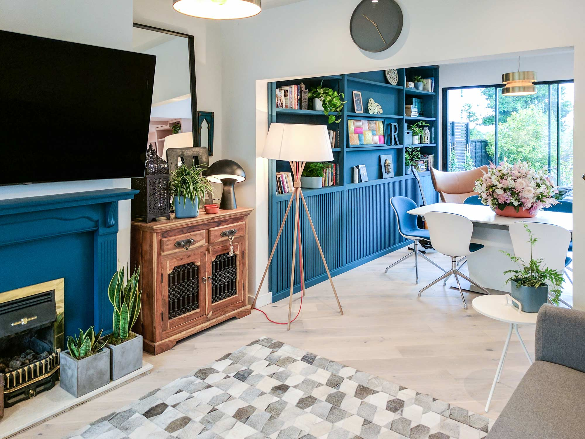 Teal fireplace and bookshelf become the key focus points in the living room and dining area of the refurbished extension.