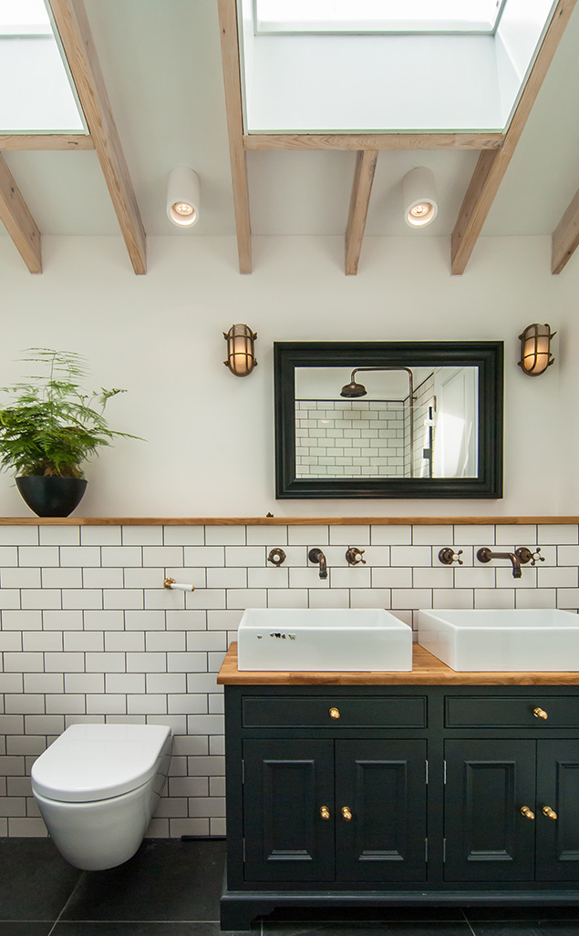 The gold brass details and interesting lighting are the key features in this renovated bathroom.