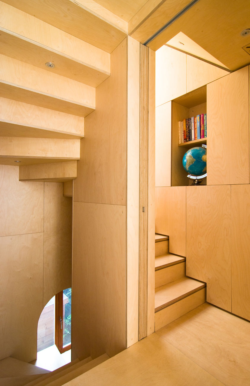 Plywood staircase including hidden sliding walls and incorporated shelving.