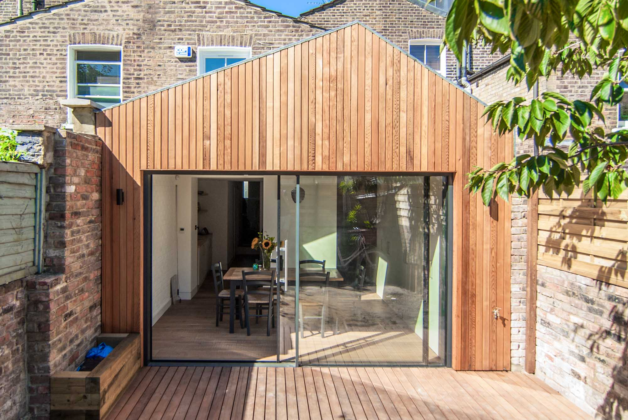 Full view of timber cladding rear extension with large sliding doors.