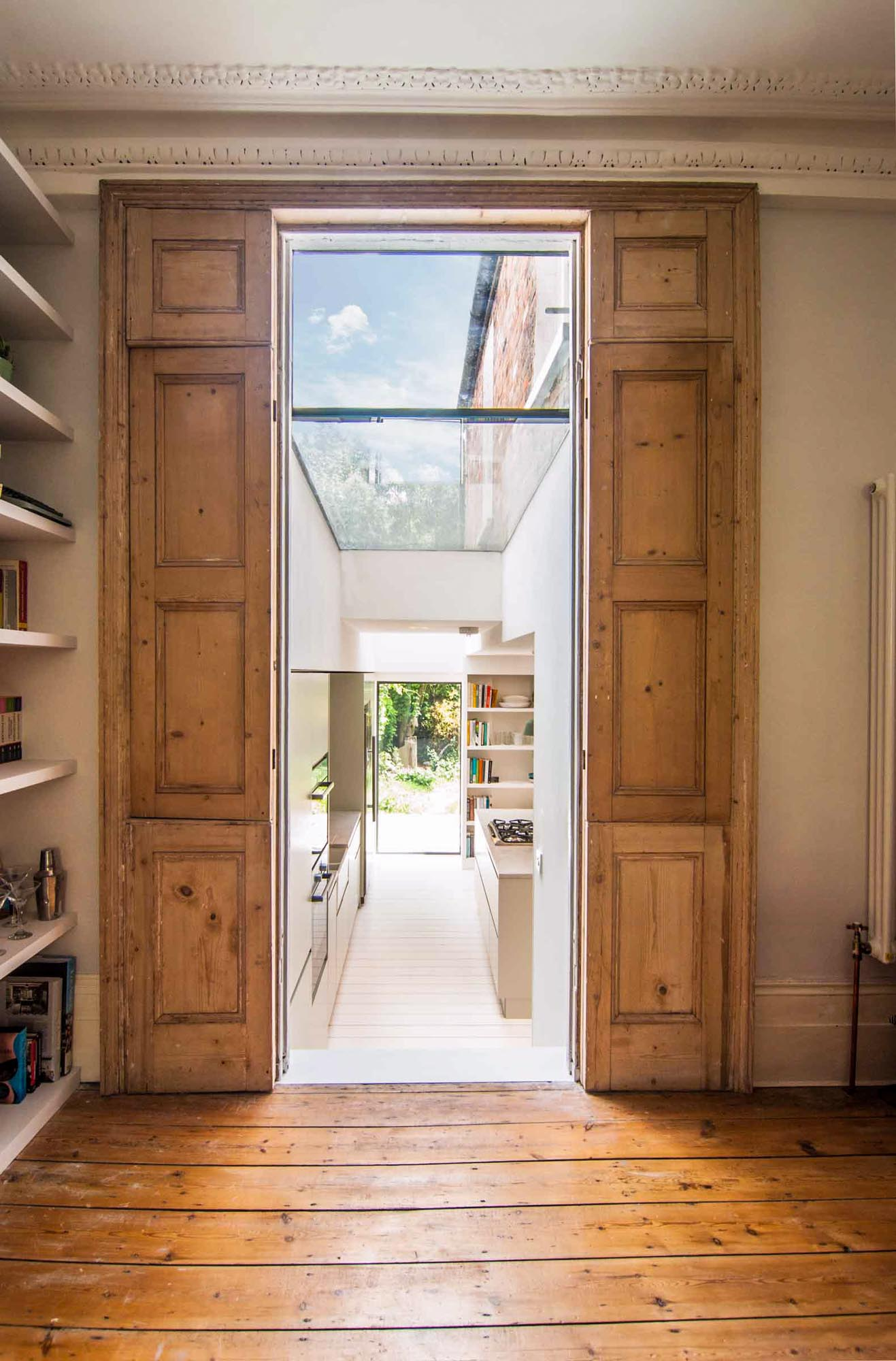 Photographer's House: Rustic door opening to the contrasting new kitchen extension.