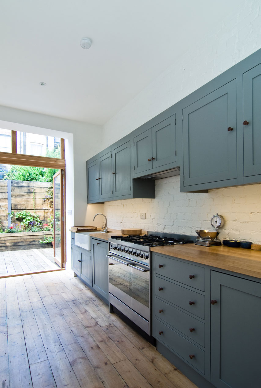 Blue kitchen cabinets stand out against the white walls and rustic floorboards.