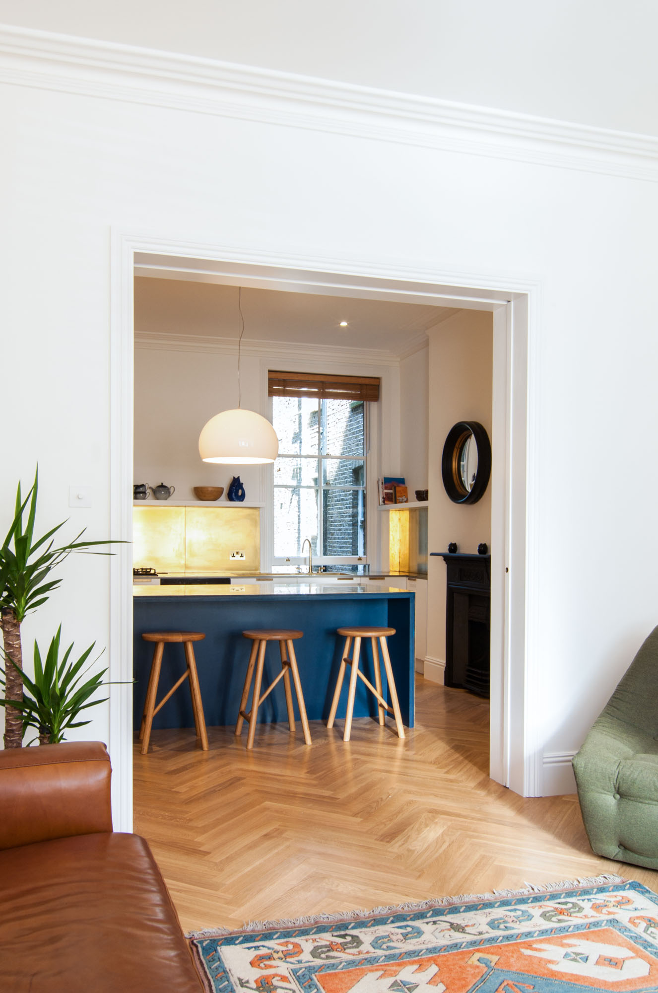 The teal and gold brass kitchen view from the colourful and bright living space.