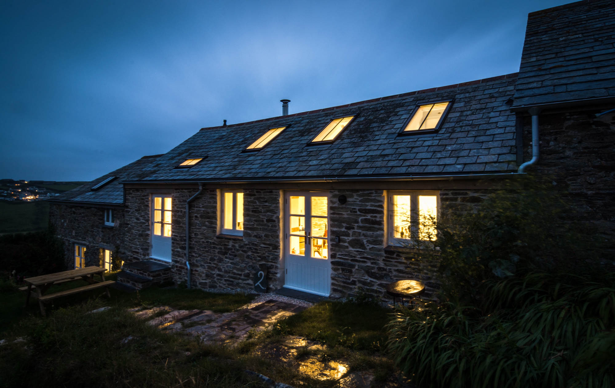 Exterior view of the cottage facade at night showing the new windows.