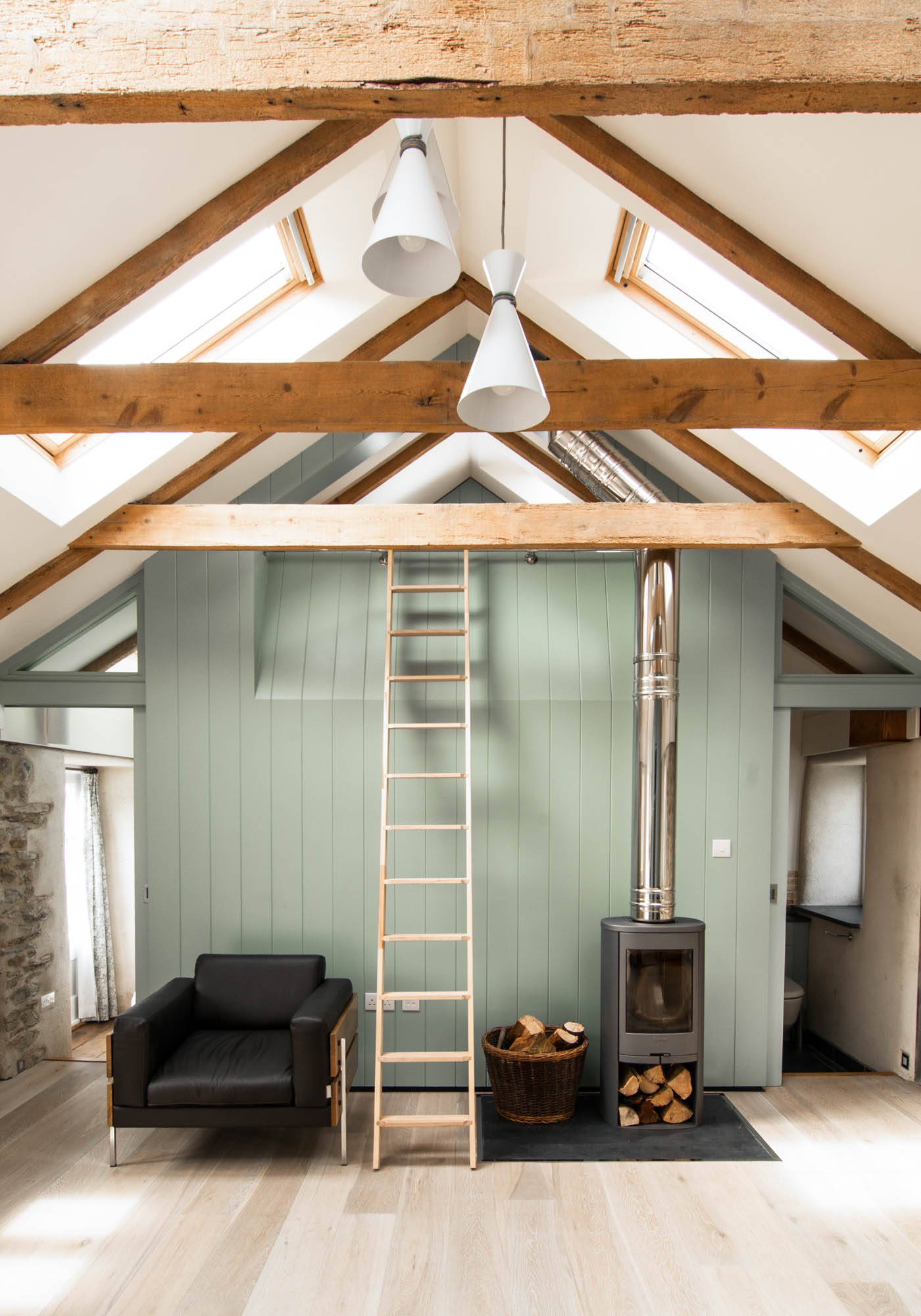 Roof lights reflecting daylight onto the light green structure and exposed beams.