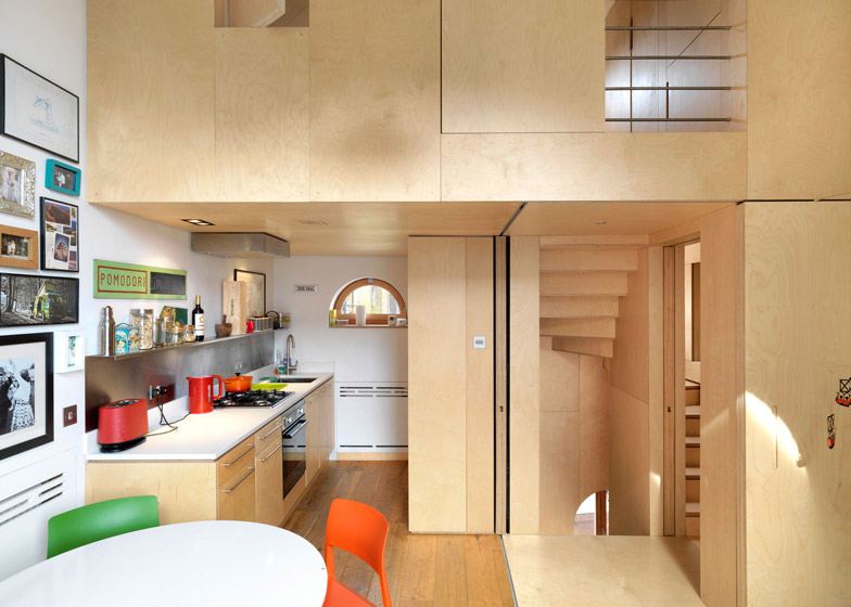 Internal view of the open kitchen and living space mostly made out of Plywood.