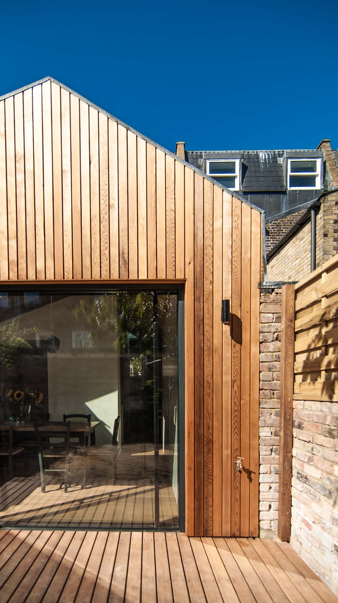 Exterior view of a timber cladding rear extension including large sliding doors.